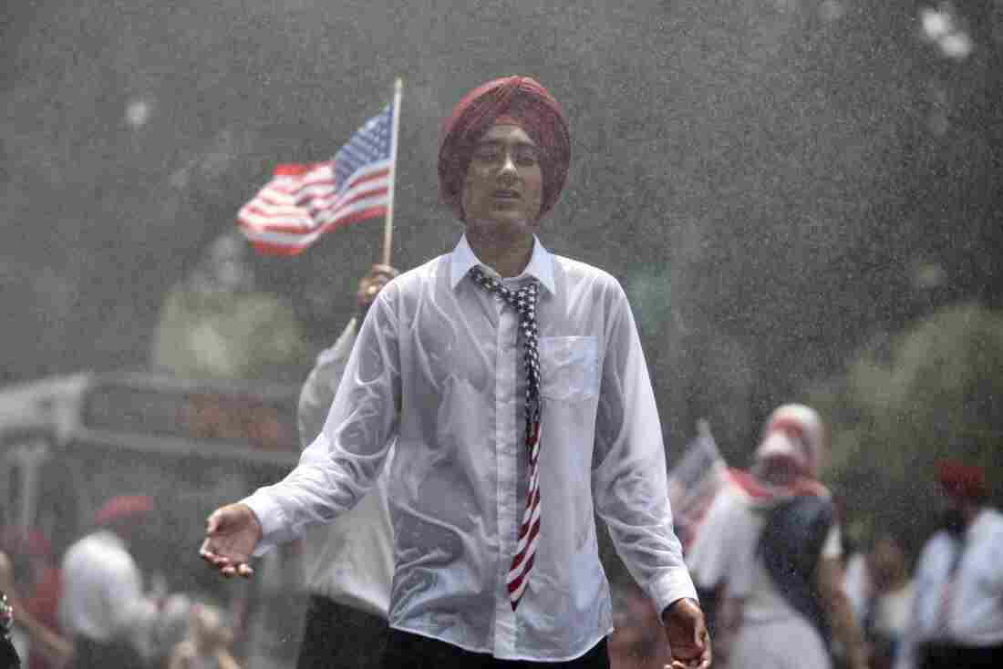 A man wearing a stars-and-stripes tie is drenched in rain during the National Independence Day Parade.