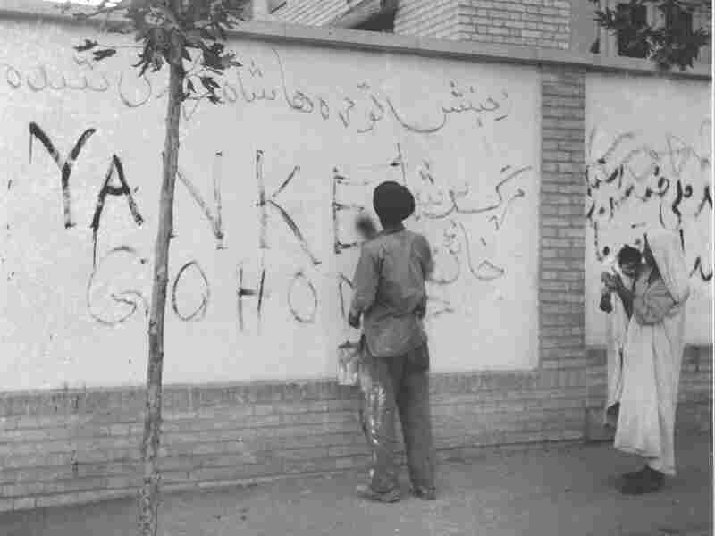 "Aug. 21, 1953: A resident of Tehran washes ""Yankee Go Home"" from a wall in the capital city of Iran. The new Prime Minister Fazlollah Zahedi requested the cleanup after the overthrow of his predecessor."