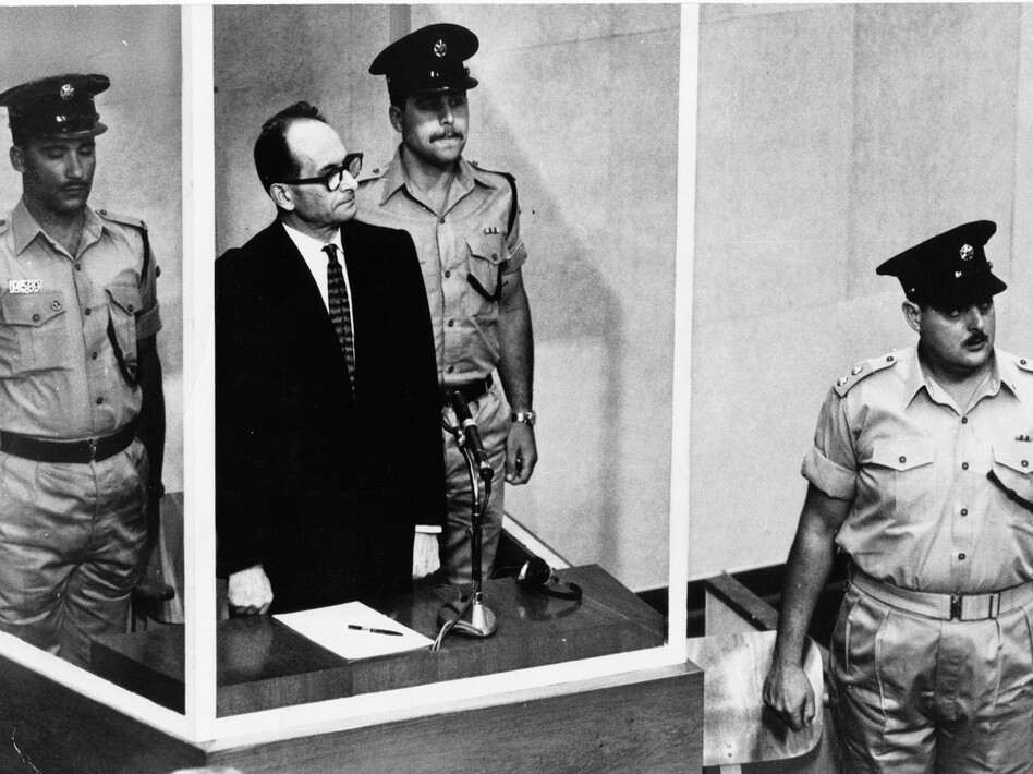Adolf Eichmann, standing in a glass booth and flanked by guards, in the Jerusalem courtroom during his trial in 1961 for war crimes committed during World War II. (AP)