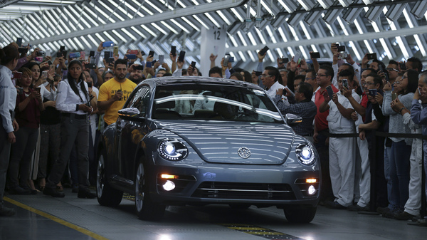 """Employees take photos of the Final Edition version of the Volkswagen Beetle, painted """"stonewash blue"""" according to the company, as it rolls out at the production plant in Puebla, Mexico. The last Beetle is not for sale, but destined instead for a museum."""