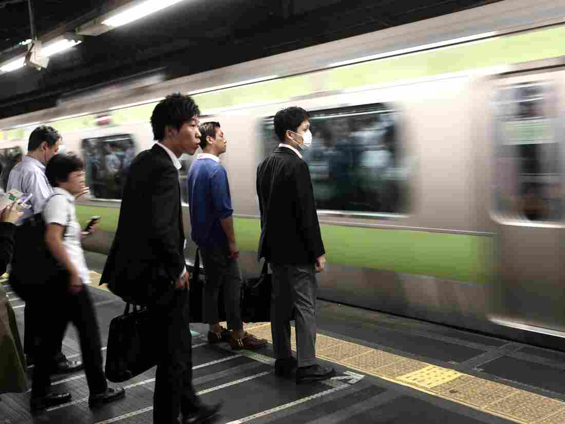 In this picture taken on October 12, 2017, people wait for the train at a subway station in Tokyo.