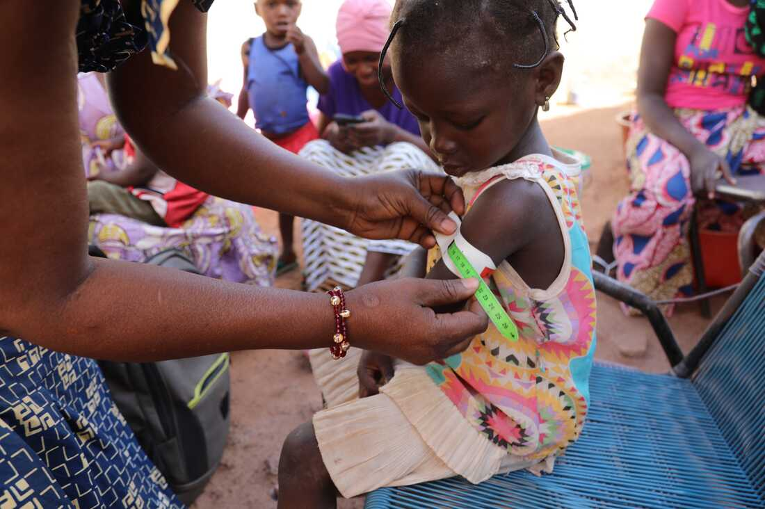Nana Kadidia Diawara, a nurse who is a community health worker in Mali's capital city of Bamako, measures the arm of a child to check for signs of malnutrition. There's no charge for the care she provides.