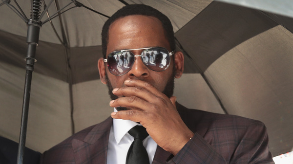 R&B singer R. Kelly covers his mouth as he speaks to members of his entourage as he leaves the Leighton Criminal Courts Building following a hearing on June 26, 2019 in Chicago.
