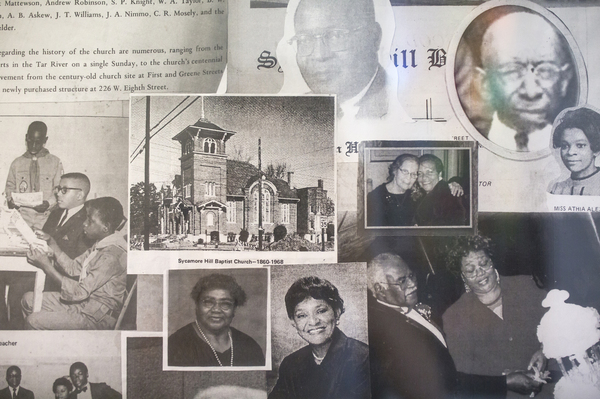 Images of former congregants as well as an image of the church's former building hang on the wall at Sycamore Hill Missionary Baptist Church.