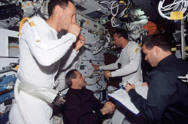 Astronauts James H. Newman (left) and Michael J. Massimino wear the liquid cooling and ventilation garment that complements the spacesuit during a 2002 mission. Also pictured on the Columbia space shuttle are pictured are astronauts John M. Grunsfeld (right) and Richard M. Linnehan.