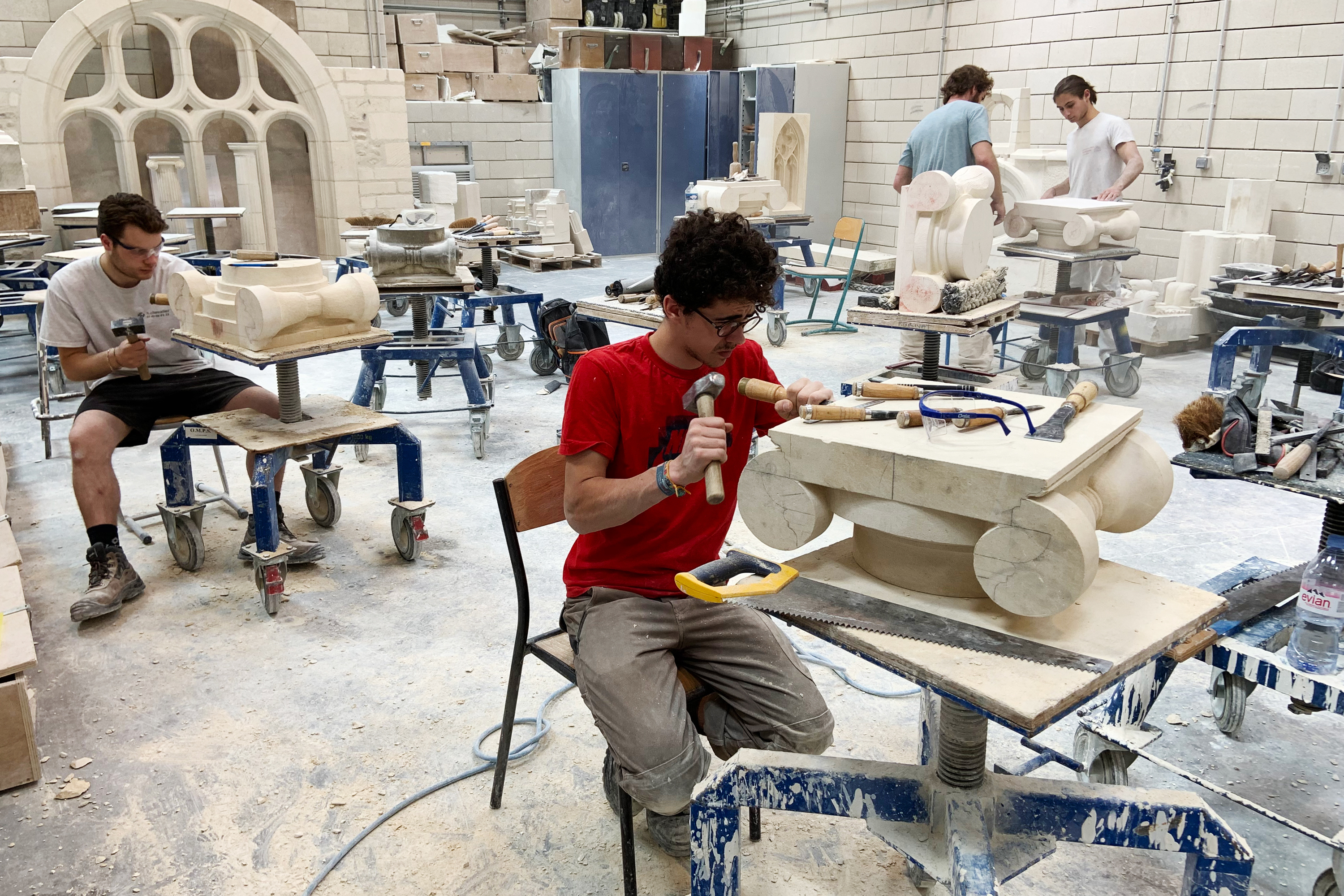 Students chip and chisel away at heavy slabs of stone in the workshops of the Hector Guimard high school, less than three miles from Paris' Notre Dame cathedral.