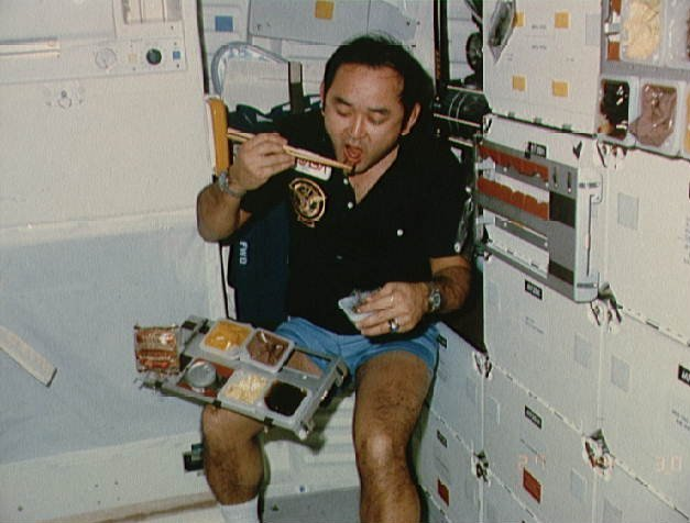 Mission specialist Ellison S. Onizuka takes a break on the mid-deck of the Discovery space shuttle during the STS 51-C mission in the 1980s.