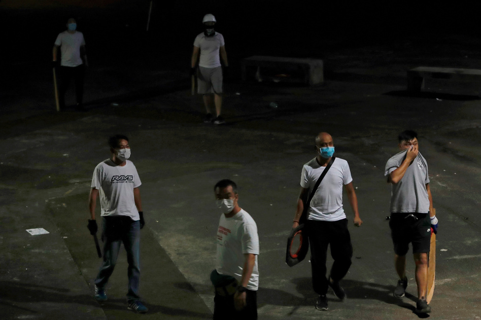 Men in white T-shirts with poles are seen in Yuen Long after clashing with anti-extradition bill demonstrators at a train station in Hong Kong. (Tyrone Siu/Reuters)