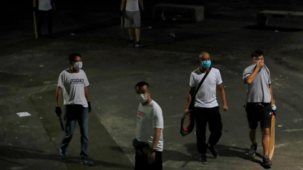 Men in white T-shirts with poles are seen in Yuen Long after clashing with anti-extradition bill demonstrators at a train station in Hong Kong.