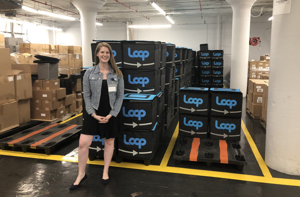 TerraCycle's Heather Crawford stands next to boxes of tote bags for a pilot project called Loop. The bags are filled with products in reusable containers and mailed to customers, who then return the bags and empty containers to be cleaned and refilled.