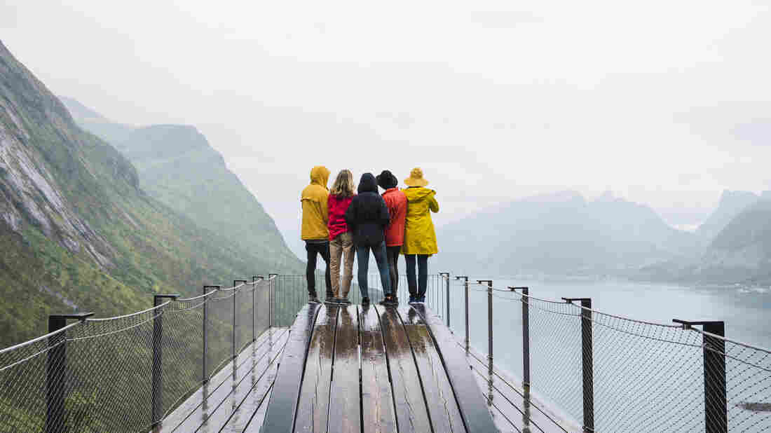 Friends stand on an observation deck on Senja Island, Norway. When traveling as a group, align your expectations ahead of time.