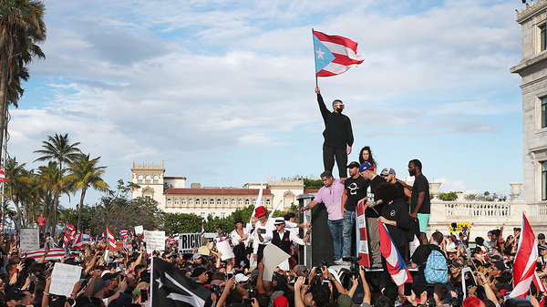 Bad Bunny (holding flag), singer Ricky Martin (in black hat) and Residente (in blue hat) join demonstrators in protest against Puerto Rico Gov. Ricardo Rosselló in Old San Juan.