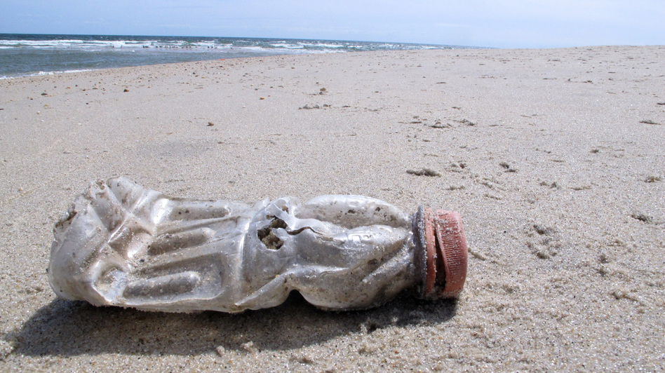 A discarded plastic bottle lies on the beach at Sandy Hook, N.J. Packaging is the largest source of the plastic waste that now blankets our planet. (Wayne Parry/AP)