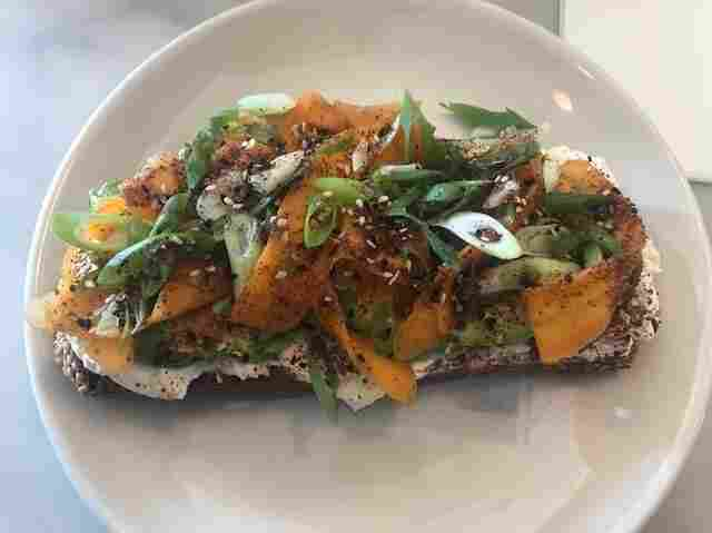 Sqirl, a popular eatery in LA's Silver Lake neighborhood, is known for its avocado toast. It features an entire avocado on a thick slice of country bread from a local bread-maker, with garlic creme fraiche and topped with hot pickled carrots and homemade za'atar.