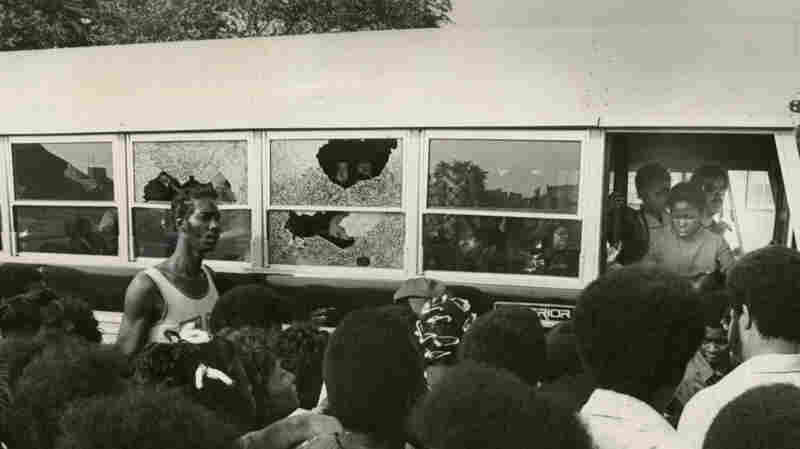 A crowd watches as a bus carrying students returns to Columbia Point with broken windows on September 12, 1974, the first day of school under the new busing system. The system was met with strong resistance from many residents of Boston neighborhoods.