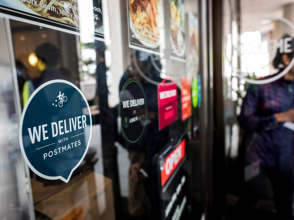 A restaurant in San Francisco displays the logo of Postmates food delivery company.