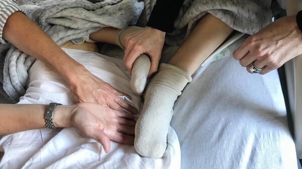 Robyn Adcock (left), a University of California, San Francisco pain relief specialist, gently guides Jessica Greenfield to acupressure points on her son