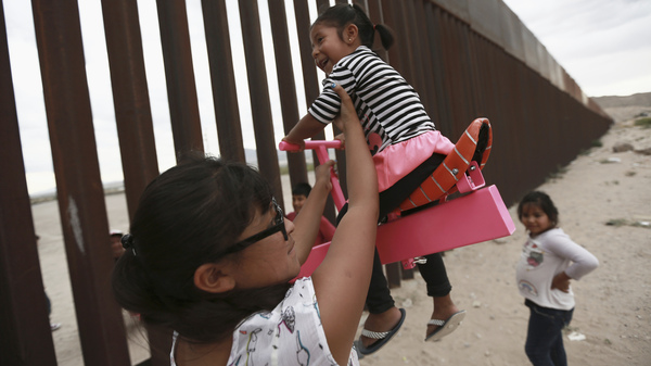 A set of pink seesaws allowed people to share some fun along the U.S.-Mexico border wall this week. Here, a woman helps her little girls ride the seesaw that was installed near Ciudad de Juarez, Mexico.