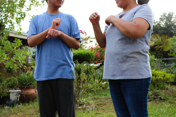 A Guatemalan teen asylum-seeker (left), who isn't able to hear or speak, signs with his mom in Florida. He was brusquely separated from her and held in a shelter for nearly three months, unable to readily communicate, according to a civil rights complaint filed with the Department of Homeland Security.