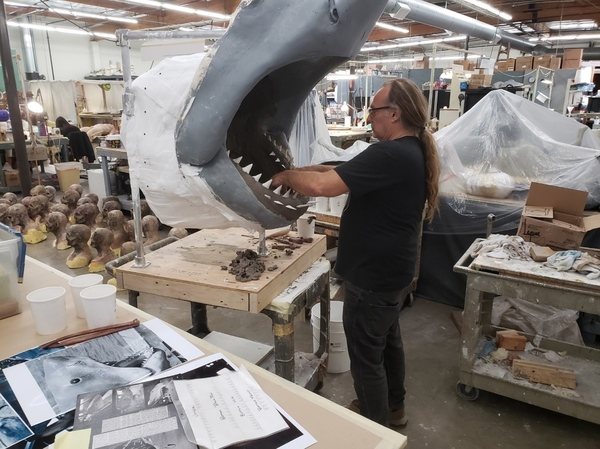 Greg Nicotero risks his safety to sculpt a new mouth for the museum-bound Bruce. Notice the army of zombie heads on the floor to Nicotero's left, awaiting use for an episode of The Walking Dead.