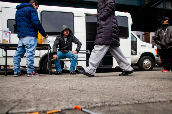A bus run by the organization Prevention Point parks at Kensington and Allegheny avenues in Philadelphia to offer harm-reduction services to drug users in the area. Louis Morano (center), who was visiting the Prevention Point bus for the second time, sits outside and waits to be seen by Dr. Ben Cocchiaro.