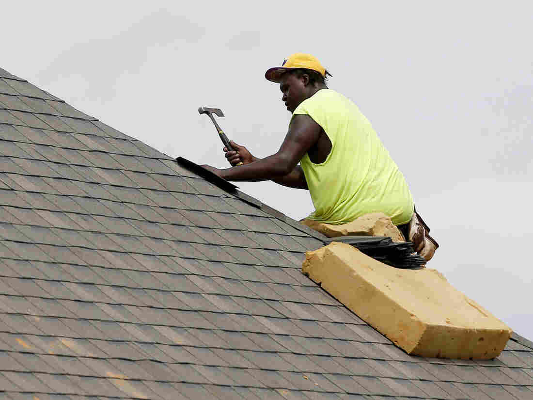 A construction worker lays down shingles on the roof of a new house in Brandon, Miss., on June 19.