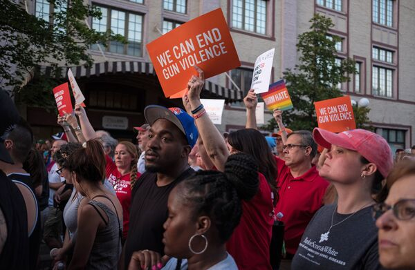 People hold signs calling for an end to gun violence during a vigil on Sunday follow a mass shooting in Dayton, Ohio.