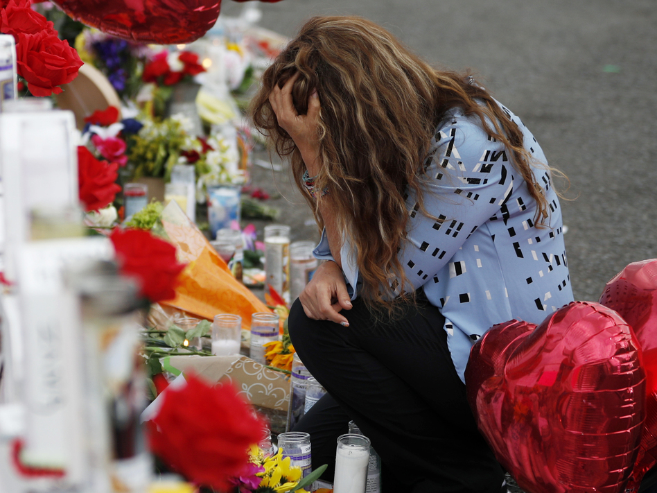 Gloria Garces kneels Tuesday in front of crosses at a makeshift memorial near the scene of a mass shooting at a shopping complex in El Paso, Texas. (John Locher/AP)