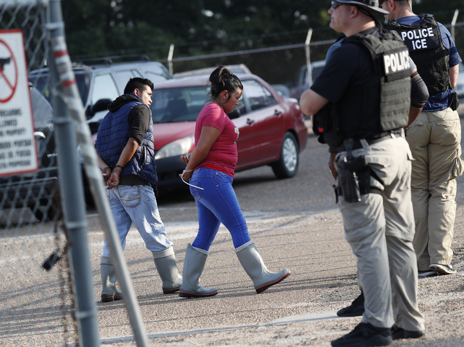 Two people are taken into custody by ICE agents at a Koch Foods Inc. plant in Morton, Miss., one of seven food processing plants targeted for coordinated raids in the state. (Rogelio V. Solis/AP)