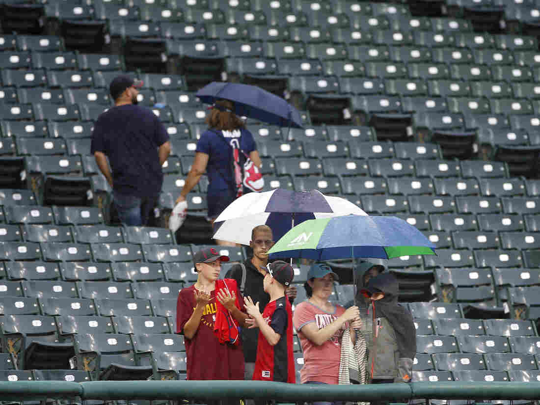 CLEVELAND, OH - AUGUST 06: Fans stand in the rain before the start of the Texas Rangers at Cleveland Indians game at Progressive Field on August 6, 2019 in Cleveland, Ohio. The game was postponed.
