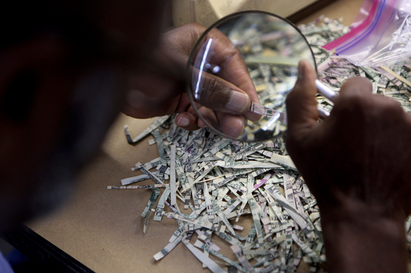 An employee of the U.S. Treasury's Mutilated Currency Division inspects shredded dollar bills to evaluate whether the damaged money should be reimbursed. The division issues an average of $30 million a year to owners of damaged bills.