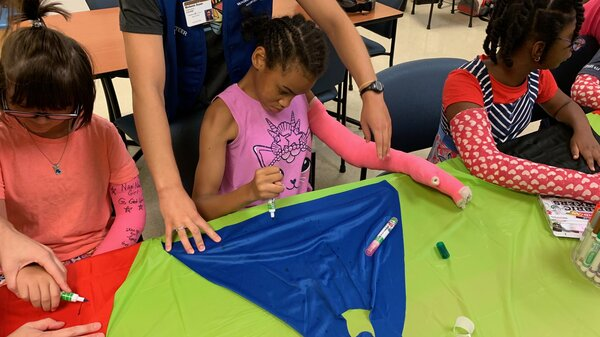 """At Nashville's """"High Five"""" camp, 12-year-old Priceless Garinger (center), whose right side has been weakened by cerebral palsy, wears a full-length, bright pink cast on her left arm — though that arm's strong and healthy. By using her weaker right arm and hand to decorate a cape, she hopes to gain a stronger grip and fine motor control."""