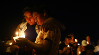 People attend a candlelight prayer vigil outside Immanuel Baptist Church, located near the scene of the mass shooting on August 5, 2019 in El Paso, Texas.