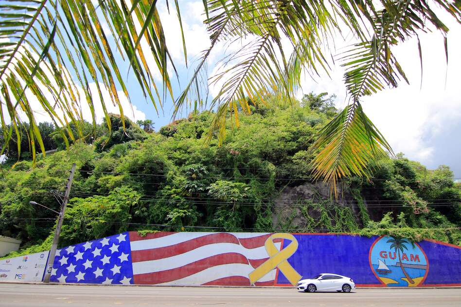 Afternoon traffic passes in front of a mural depicting the U.S. and Guam flags in the Tumon district on the island of Guam. (Virgilio Valencia/AFP/Getty Images)