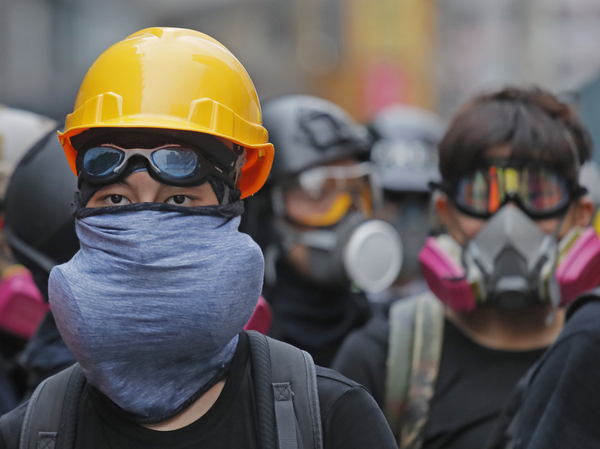 Protesters with protective gear face riot police in Hong Kong on Sunday.