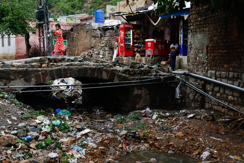 The river that once snaked through the village is now a large trash heap. (Diaa Hadid/NPR)