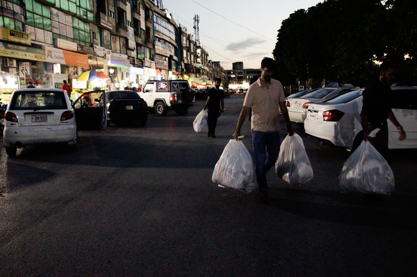 Volunteers from 5 Mailay, a group that collects trash to raise environmental awareness, pick up garbage around a strip mall in Islamabad.