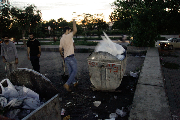Volunteers throw bags of trash they've collected into a garbage dumpster.