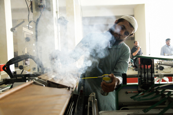 A worker operates a machine at a plastic bag factory on the outskirts of Islamabad.