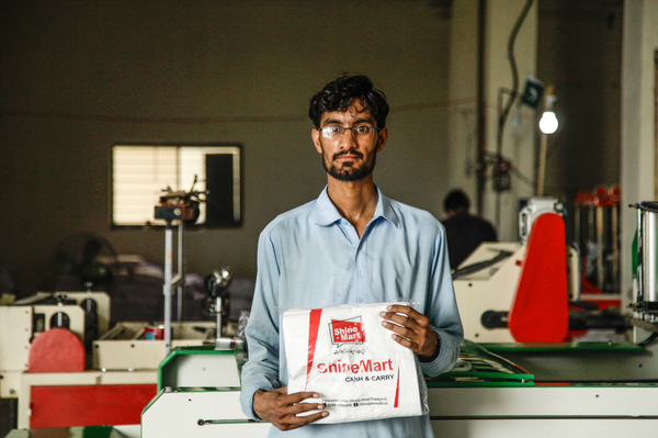 "Mohammad Zaheer holds up bags freshly stamped with supermarket slogans. He says he's worried about his future after the plastic bag ban begins. He says that if he has to find another job, ""it will be difficult, because there is much unemployment."""