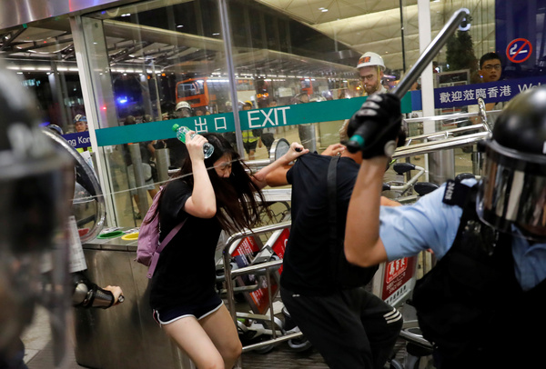 Riot police use pepper spray to disperse protesters at the airport.