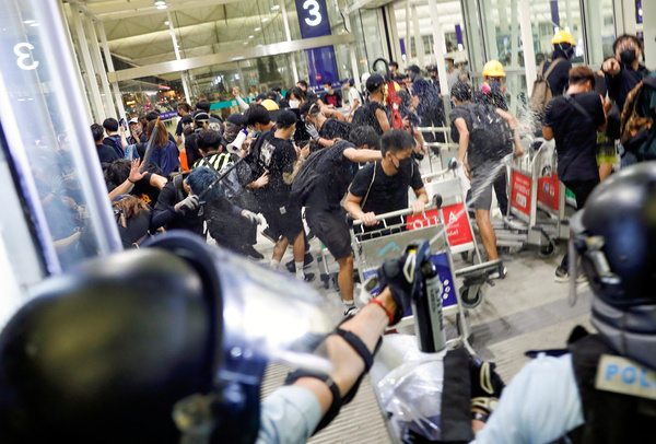 Riot police use pepper spray to disperse protesters during a mass demonstration at the Hong Kong International Airport.