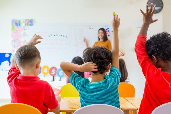 Children raise their hands in a classroom setting.