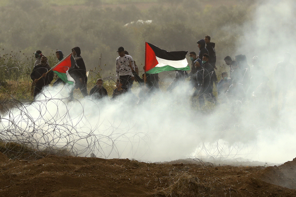 """Palestinian protesters wave national flags as they demonstrate to mark the first anniversary of the """"March of Return"""" protests. Tens of thousands of Gazans gathered along the Israeli border to mark a year since protests and clashes erupted there, days ahead of an Israeli general election."""
