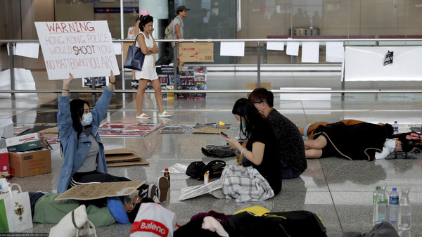 A protester shows a placard to travelers as demonstrations continue at Hong Kong International Airport on Wednesday. Flight operations resumed at the airport Wednesday morning after two days of disruptions.