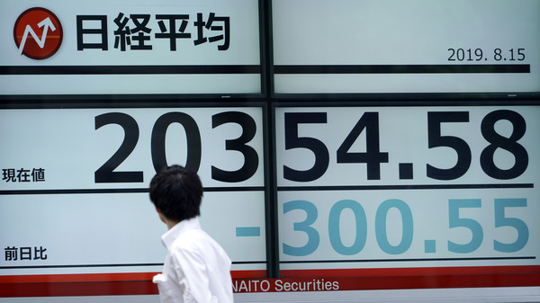 A man looks at an electronic stock board showing Japan