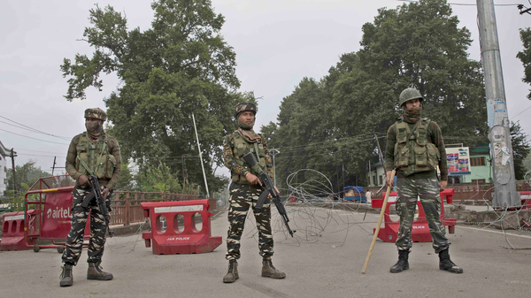 Indian paramilitary soldiers stand guard near a temporary check point on the road leading toward an Independence Day parade venue during lockdown in Srinagar, in Indian-controlled Kashmir, on Thursday. Indian Prime Minister Narendra Modi says that stripping the disputed Kashmir region of its statehood and special constitutional provisions has helped unify the country.