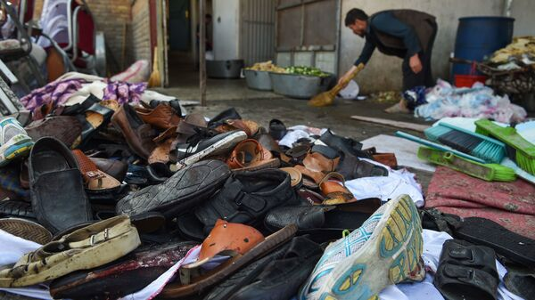 A man cleans an area next to a pile of shoes and sandals of victims outside a wedding hall after a deadly bomb blast in Kabul.