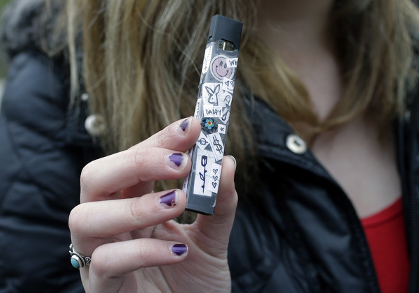 A 15-year-old in Cambridge, Mass., shows off her vaping device in 2018. Schools and health officials across the U.S. are struggling to curb what they say is an epidemic of underage vaping.
