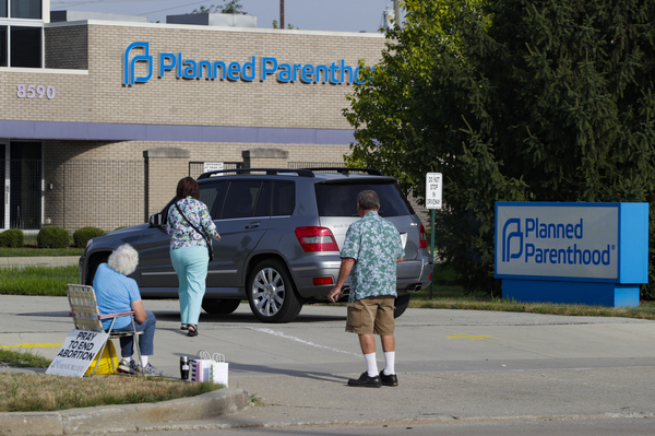 Abortion protesters attempt to handout literature as they stand in the driveway of a Planned Parenthood clinic in Indianapolis on Aug. 16, 2019.